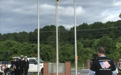The Hereford and Woodlawn Chamber Choir sing the National Anthem as ROTC members raise the flag.