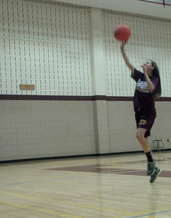 """Shoot for the stars: Caroline Peterson (9) shoots a layup in her second period gym class. Coach Kaylisz has been working with these 9th graders, teaching them proper techniques for shooting a basketball. """"I just like shooting"""" said Caroline. Coach K later went on to teach dribbling skills."""