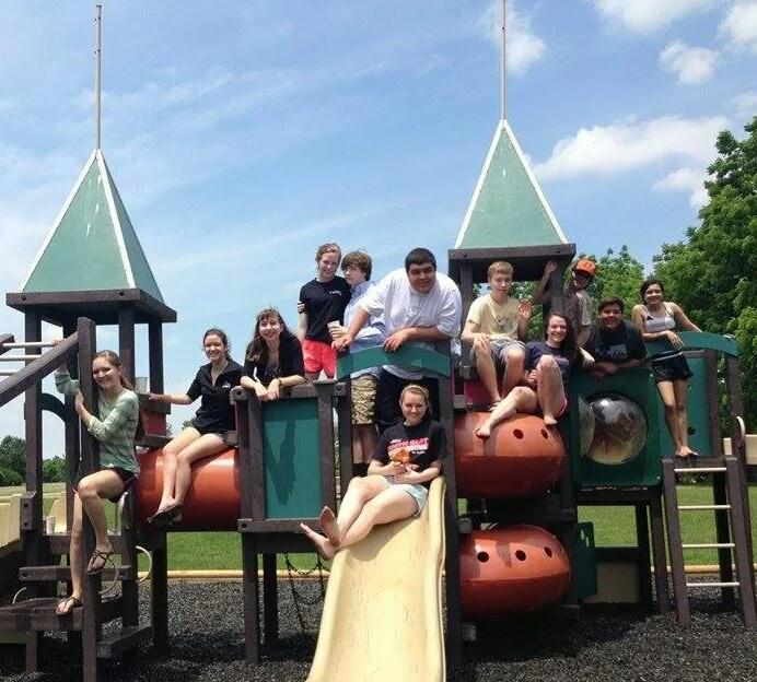 High school members of the cast pose for a photo, taking a break on the playground during an 8 hour rehearsal.
