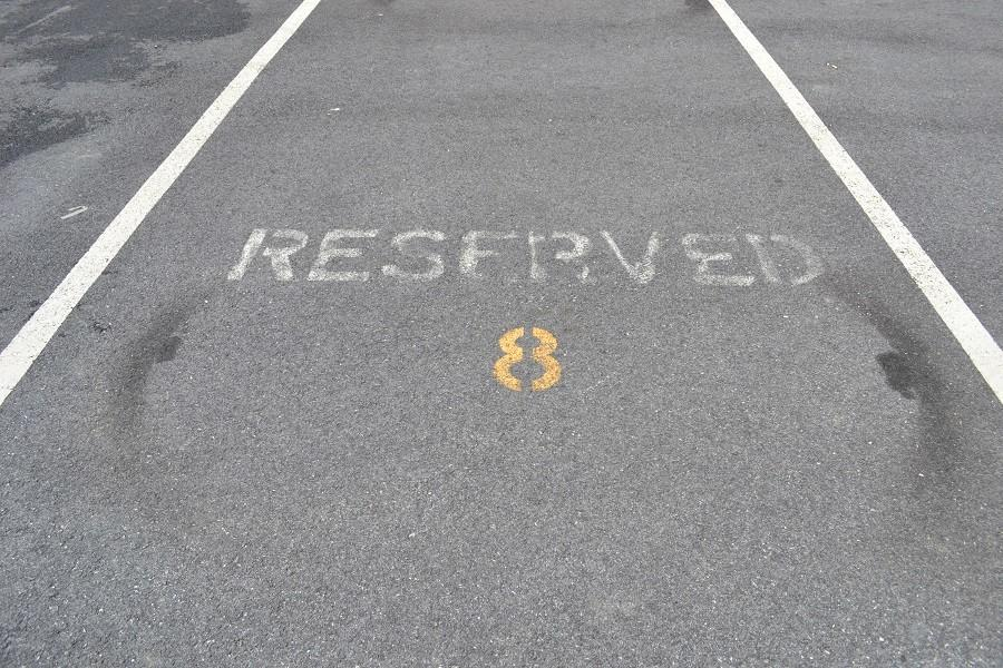 Reserved parking spots are left empty while the student lot is filled. Students felt frustrated when they drove past  unoccupied spots.