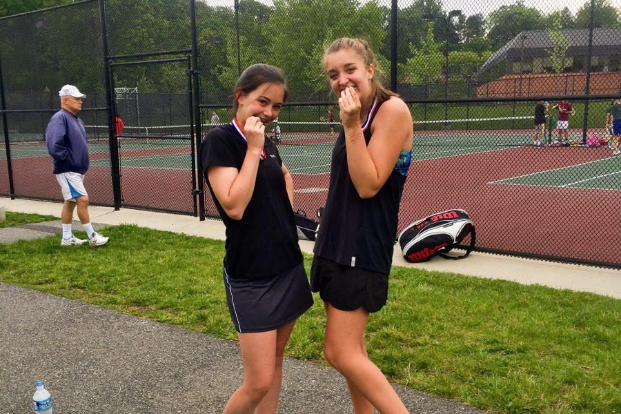Benson and Reider bite their medals they received for coming in first place for the girls doubles two court in the Baltimore County Tennis Championship.