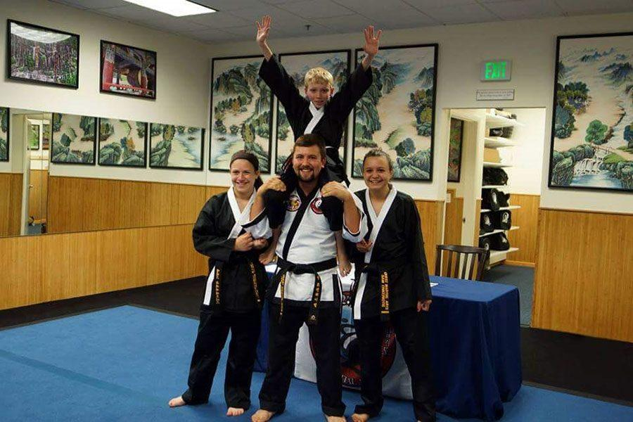 Alex Trikeriotis ('18) poses with her friends at Quest Martial Arts. They just passed their black belt test and received their black belts.