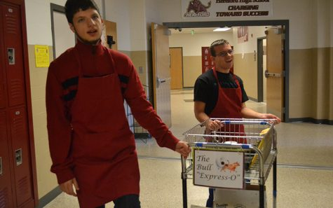 Silas Rock (17) and Jackson (17) push the Bulls Expresso delivery cart through the halls. [The coffee shop] makes working at Hereford even better, Social Studies teacher Robert Greenwood said. For teachers participating in the secret Santa gift exchange, Clark and the Bull Express-O will deliver gifts so teachers can remain anonymous.