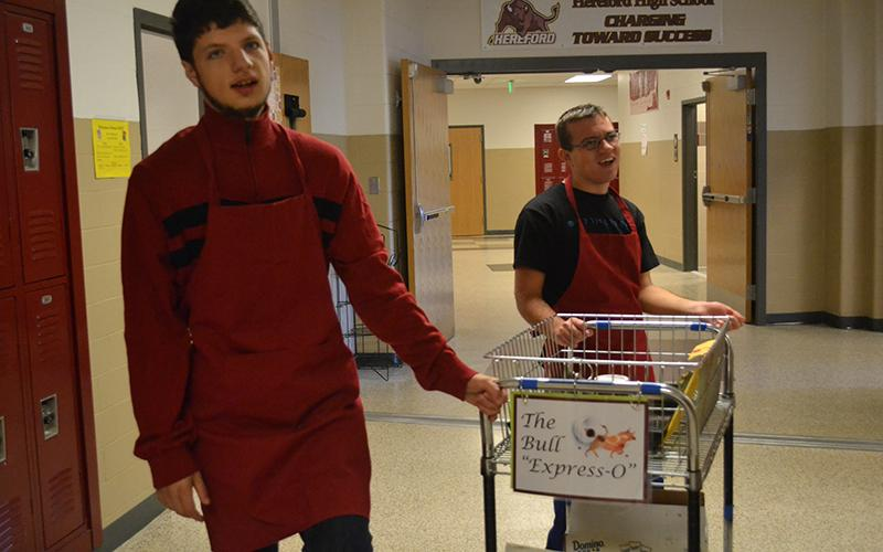 Silas Rock ('17) and Jackson ('17) push the Bulls' Expresso delivery cart through the halls.