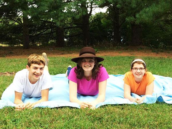 My siblings and I lie on a blanket in our backyard on a Sunday, chatting as we breathe the fresh air.