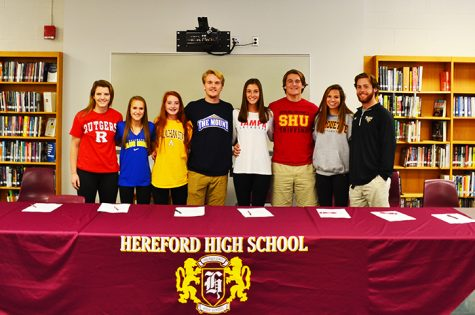 Senior athletes gather in th library on Nov. 11 to sign their national letters of intent. From left to right: Erin Collins, Kelly Wesolowski, Lauren Litsinger, Campbell Carr, Graeme Eber, Andrew Clark, Caroline Peterson, Joey Chesnutt.
