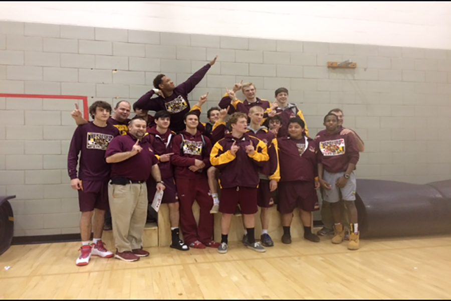 The varsity wrestling team poses for a picture after Regionals.  They competed in the tournament earlier that day.