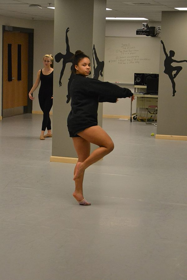 Nya Bennett ('19) warms up in the beginning of class.