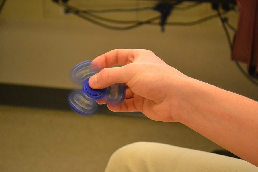 Hugh Lory ('17) spins a fidget spinner. The spinner has helped Lory use energy in class and pay attention.