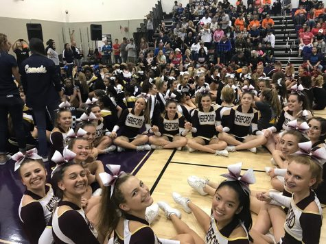 JV cheer squad circles up awaiting awards after their first invitational.