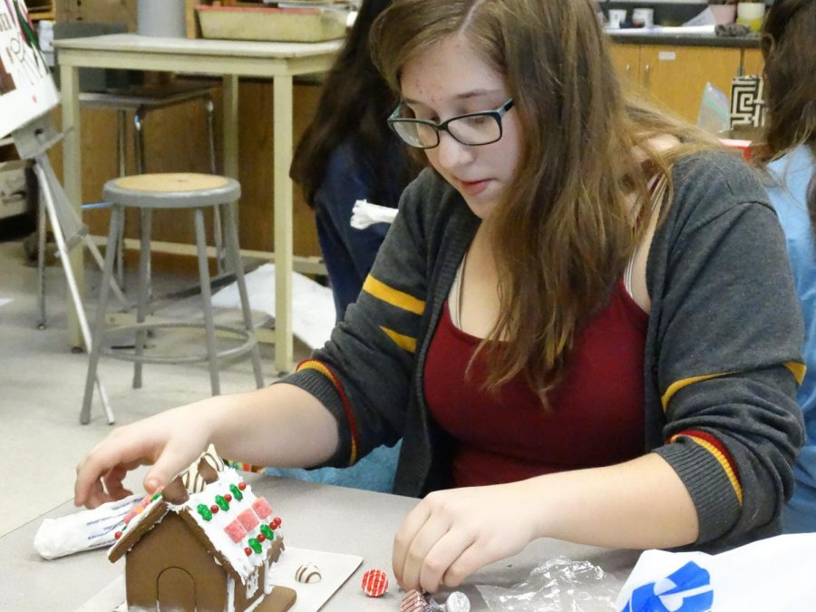 Maddie Gaede ('20) decorates her gingerbread house in NAHS.