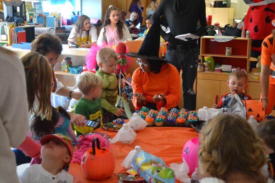 Child Development teacher, Morgan Espeut passes out cupcakes to preschoolers. They had a short break before going on a second round of trick-or-treating.