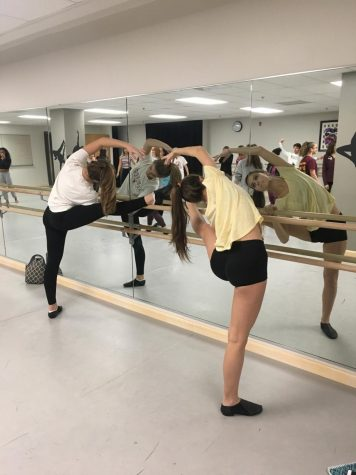 "Megan Sabo ('20) and Elsbeth Supplee ('20) stretch before Junior Dance Company practice. This is both of their first years participating in the club. ""It was really fun just to get a different set of choreography and to have dance outside of my actual class, ""Supplee said. ""It's challenging to get a piece together that quickly, but I thought it was a good challenge."""