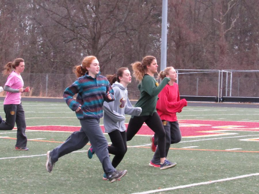 Girls track team warms up before practice. The team recently won the Warrior Invitational, as well as other meets.