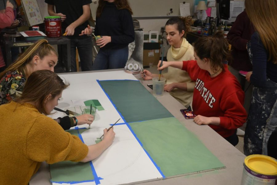 Members of the National Art Honors Society begin to fill the shapes with green paint. The finished panel was portrayed to represent a shall, to embody biology.