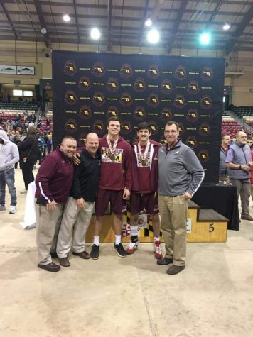 Mr. Baier and other wrestling coaches, pose with Jimmy Kells ('19) and Cale McMurdy ('18), who placed at the meet.
