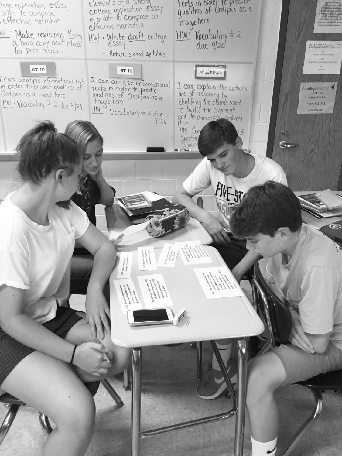 Students collaborate among each other, attempting to identify the argument, claims, and evidence in an argumentative article. This is part of the students' daily routine in Seminar, helping them get used to what they would be doing for the AP test.