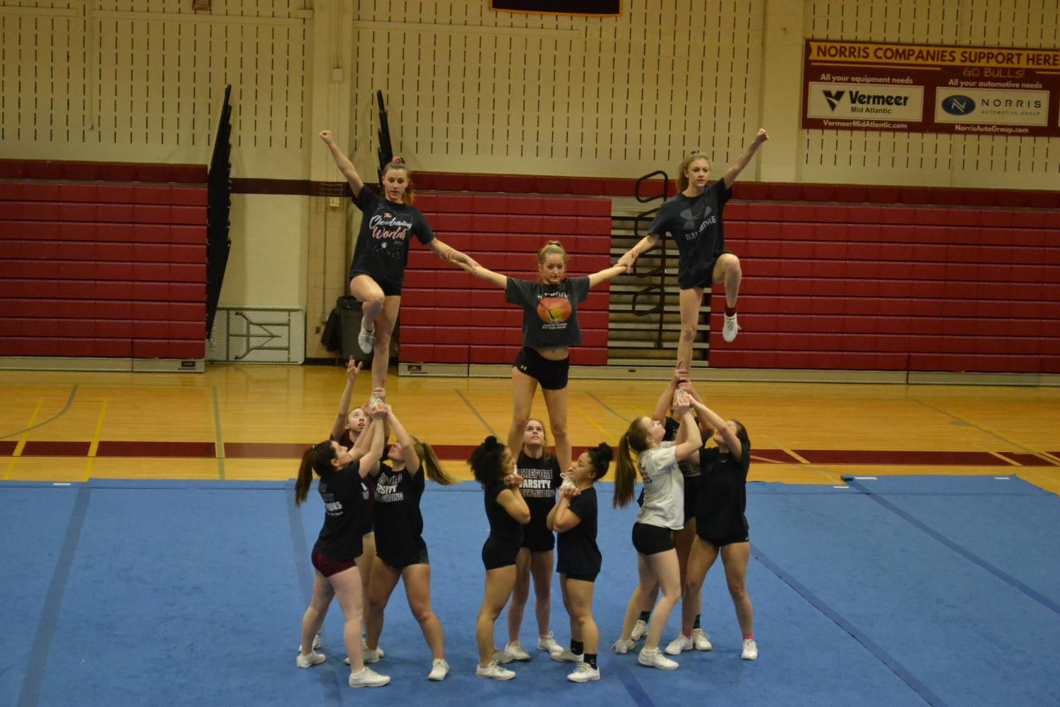 Emma DiVenti ('22) supports her teammates during their stunt. The team practiced this move daily to perfect it.