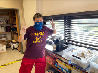 Manuel Grothe ('24) poses for a picture as he makes a coffee in Mrs. Duvall's room.