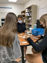 Tessa Janey (22), Caroline Sabo (22), and Brooke Sarratea (23) write messages on small tags to attach to carnation stems. Club members worked to quickly get everything done on Thursday in order for the event to run smoothly Friday.